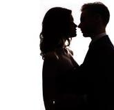 Silhouettieren Sie vlublennoj glückliches Paar, das auf einem weißen Hintergrund küsst Stockfotografie