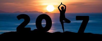 Silhouettieren Sie Yoga Spiel der jungen Frau auf dem Meer und dem guten Rutsch ins Neue Jahr 2017 beim Feiern des neuen Jahres Stockfotografie