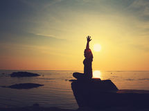 Silhouettieren Sie Yogamädchen durch den Strand bei dem Sonnenaufgang, der Meditation tut Lizenzfreies Stockbild