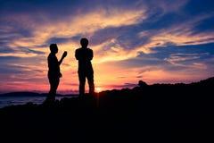 Silhouettieren Sie Zwei-mannstellung auf dem clift während des Sonnenuntergangs Lizenzfreies Stockfoto