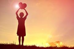 Silhouettiert ein Mädchen, das Herzform hält stockfoto