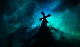 Silhouettiert Menge von hungrigen Zombies und von alter Windmühle auf Hügel gegen dunklen nebeligen getonten Himmel Schattenbilde Stockfoto