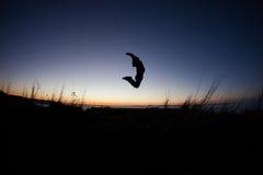 Silhouettiert vom Mann, der in Sonnenuntergang springt stockfotografie
