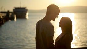 Silhouettierte Paare halten sich und küssen auf dem Strand Datum an der Seeseite stock video footage