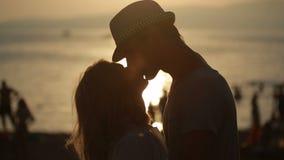 Silhouettierte Paare halten sich und küssen auf dem Strand Datum an der Seeseite stock video