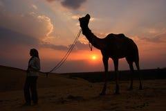 Silhouettierte Person mit einem Kamel bei Sonnenuntergang, Thar-Wüste nahe Jais Lizenzfreies Stockbild