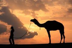 Silhouettierte Person mit einem Kamel bei Sonnenuntergang, Thar-Wüste nahe Jais Stockfotografie