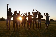 Silhouettierte Schulkinder, die draußen bei Sonnenuntergang springen stockbild