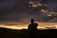 Silhouettierte Zahl einer Person gegen einen Sonnenuntergang Stockbild