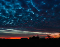 Silhouettierter Bauernhof mit bewölktem Sonnenuntergang Stockfotos
