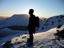 Silhouettierter Bergsteiger auf schneebedecktem Gebirgsgipfel lizenzfreies stockbild