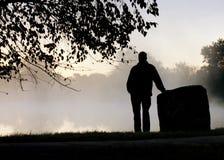 Silhouettierter erwachsener Mann steht allein durchdacht, anstarrend in Richtung zum nebeligen See Stockbild