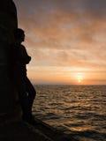 Silhouettierter junger Mann überwacht Sonnenaufgang von einem Pier. Lizenzfreies Stockfoto
