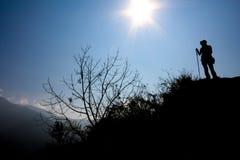 Silhouettierter Trekker, der die Höhe anficht Lizenzfreies Stockfoto