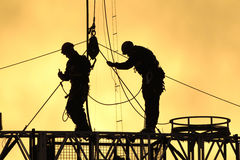 Silhouettte workers 01. Two workers climb to fix the lines at stadium in the sunset Stock Photos