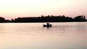 Silhouetvisser op boot die vissen in rivier op achtergrondavondzonsondergang vangen stock footage