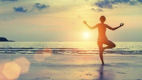 Silhouetvrouw het praktizeren yoga op het overzeese strand bij surrealistische zonsondergang Stock Foto's