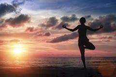 Silhouetvrouw het praktizeren yoga op het overzeese strand bij verbazende bloedige zonsondergang Royalty-vrije Stock Fotografie