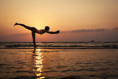 Silhouetvrouw het praktizeren yoga op het strand Royalty-vrije Stock Fotografie