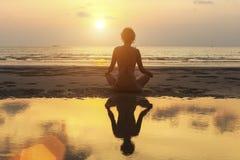 Silhouetvrouw het praktizeren yoga op het strand bij verbazende zonsondergang Stock Afbeelding