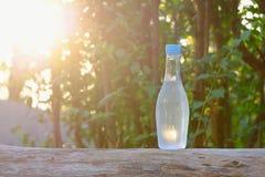 Silhouetzonlicht met een plastic fles drinkwater op een hout bij het groene park stock fotografie