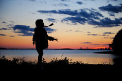 Silhouhette of a child girl walking in the sunset stock photography