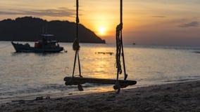Silhoute d'oscillation sur la plage avec le coucher du soleil et de mer, Mountain View en île de Pho Quoc image stock
