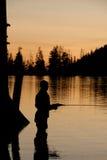 Silhoutette de pêche de mouche Photographie stock