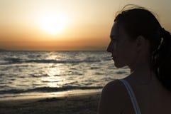 Silhoutte женщины смотря заход солнца Стоковая Фотография RF