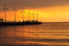 Silhoutte людей на заходе солнца около океана Стоковые Фотографии RF