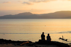 SILHOUTTE COUPLE SITTING BEACH TWILIGHT SUNSET MOUNTAINS BACKGROUND Royalty Free Stock Photos