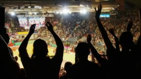 Crowd cheering at basketball stadium. Silhoutte of crowd cheering at basketball stadium royalty free stock images
