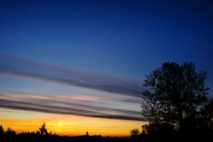 Silhoutte d'arbre et d'îles à loin avec la couleur vive du ciel pendant le coucher du soleil image stock