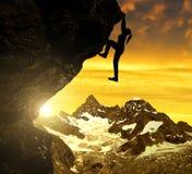 Silhoutte de la muchacha que sube en roca en la puesta del sol Imagen de archivo