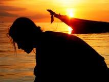 Silhoutte de la muchacha soñadora en la playa tropical de la puesta del sol   Imagenes de archivo
