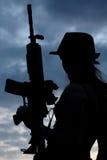 Silhoutte de la mujer con el arma Foto de archivo libre de regalías