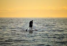 Silhoutte de se coloca para arriba de batimiento de la persona que practica surf imagenes de archivo