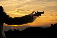 Silhoutte de un hombre con una arma de mano imagenes de archivo