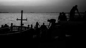 Silhoutte der Fischerarbeit am Hafen Stockbilder
