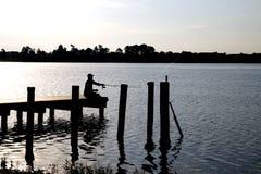 Silhoutte des Fischers auf Dock Stockfoto