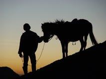 Silhoutte des Mannes und des Pferds Stockbild