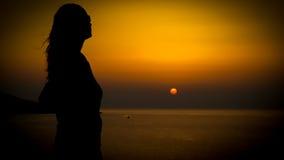 Silhoutte do por do sol da jovem mulher em uma costa foto de stock royalty free