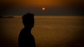 Silhoutte do por do sol do homem novo em uma costa fotos de stock
