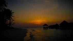Silhoutte do por do sol dos bungalows e das palmeiras fotografia de stock royalty free