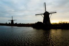Silhoutte of dutch traditional old wind mills along the river in the romantic sunset stock images