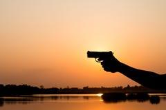 Silhoutte eines Mannes mit einer Pistole Stockfotos