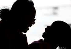 Silhoutte juguetón de la madre y de la hija Fotos de archivo