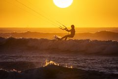 Silhoutte of kitesurfers enjoying big waves at sunset in Essaouira, Morocco. Beautiful landscape in background stock photos