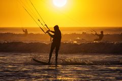 Silhoutte of kitesurfers enjoying big waves at sunset in Essaouira, Morocco. Beautiful landscape in background stock images