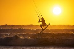 Silhoutte of kitesurfers enjoying big waves at sunset in Essaouira, Morocco. Beautiful landscape in background stock photography